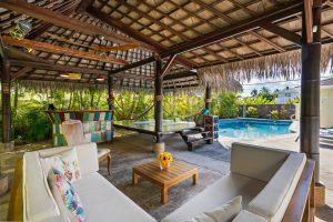 backyard oasis with cabana with sofa, deck, minibar, and swimming pool in the background