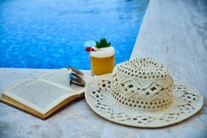 beige straw hat book sunglasses and drink beside pool 3019008